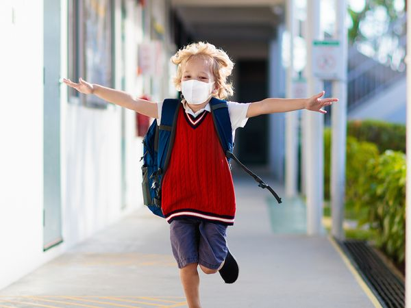 A young boy wearing a face mask at school