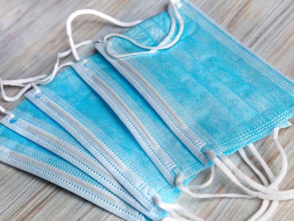 Five blue disposable face masks laying on a table