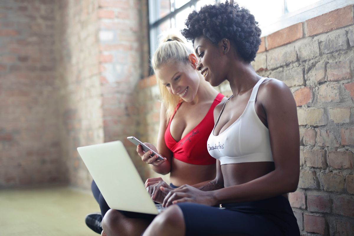Canva - Two Women Wearing Red and White Sports Bras Sitting Near Brown Wall Bricks.jpg
