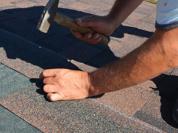 An image of a man with a hammer replacing shingles on a roof.