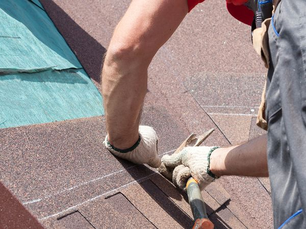 An image of a man with a hammer replacing the shingles on a roof.