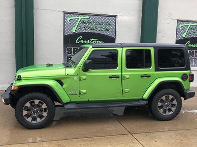 Green Jeep with tinted windows