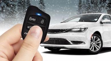 hand holding remote start button and vehicle in snowy background
