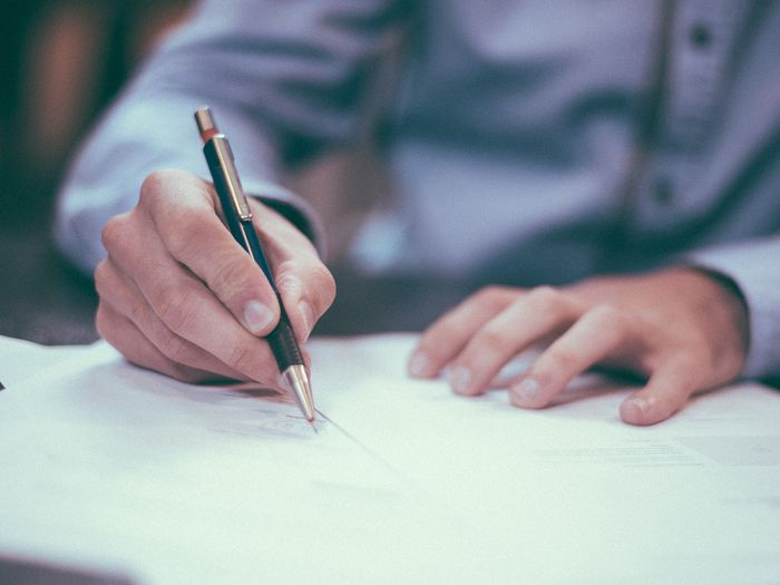 image of man signing papers