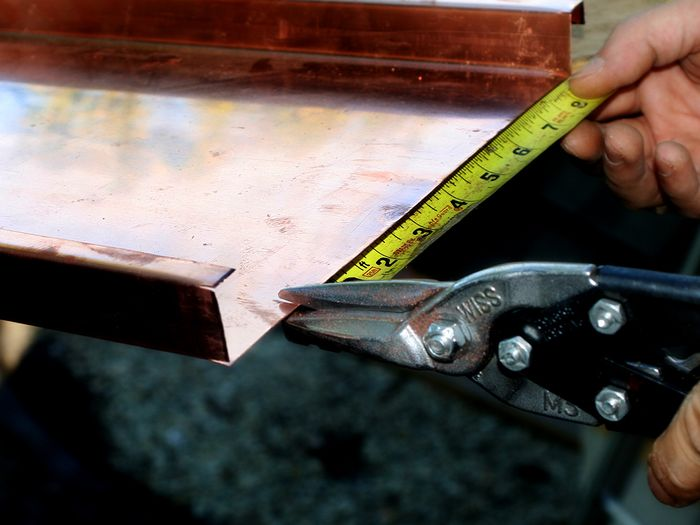 image of copper roofing materials being measured