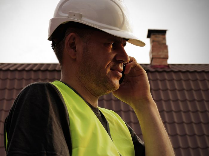 image of roofing contractor in hard hat on mobile phone