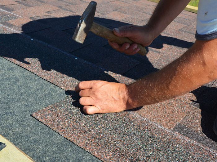image of contractor hammering down shingles on a roof