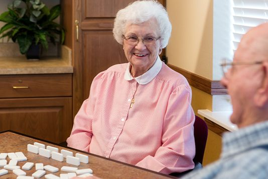 patients laughing together playing dominoes