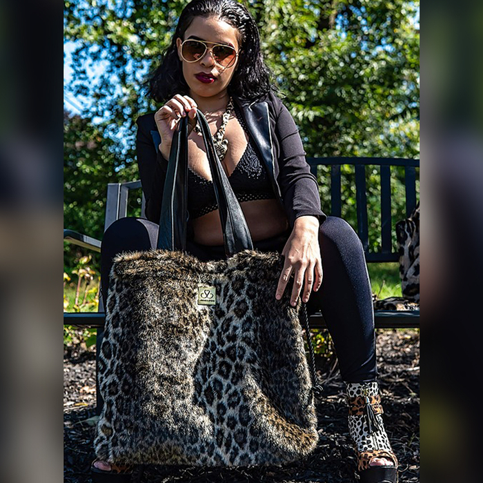 Woman holding the Shoelugg in a cheetah print design.