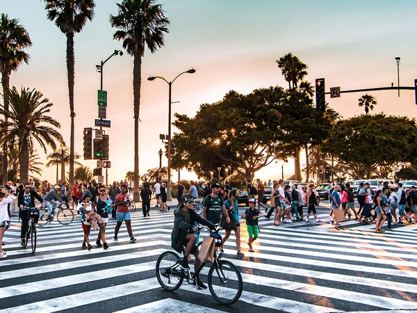 A busy intersection with people walking and riding bikes