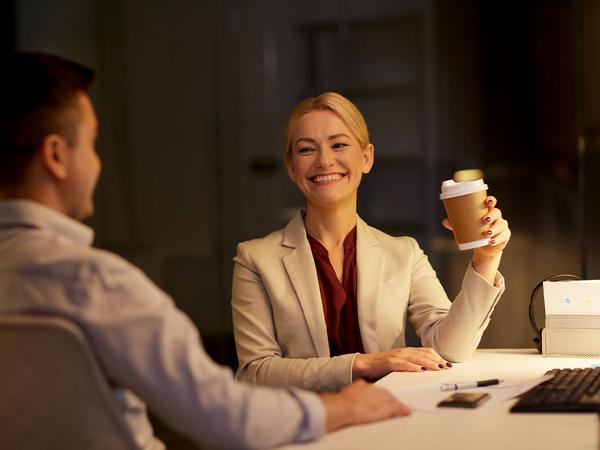 smiling businesswoman holding a cup of coffee while talking to coworker