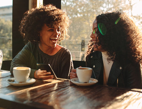 Two friends laughing over a cup of coffee