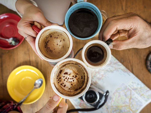 group of people clinking their coffee cups together