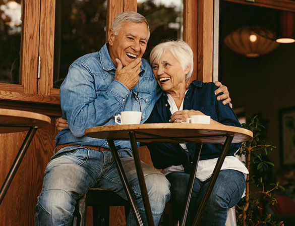 Older couple laughing outside of a coffee shop