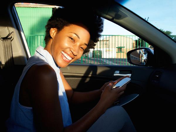 smiling woman in car using smartphone