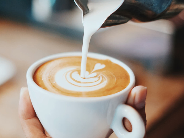 A barista at a coffee shop pouring latte art.