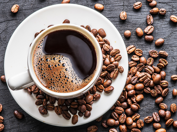 A cup of freshly roasted coffee sitting on a plate, surrounded by different kinds of coffee beans.