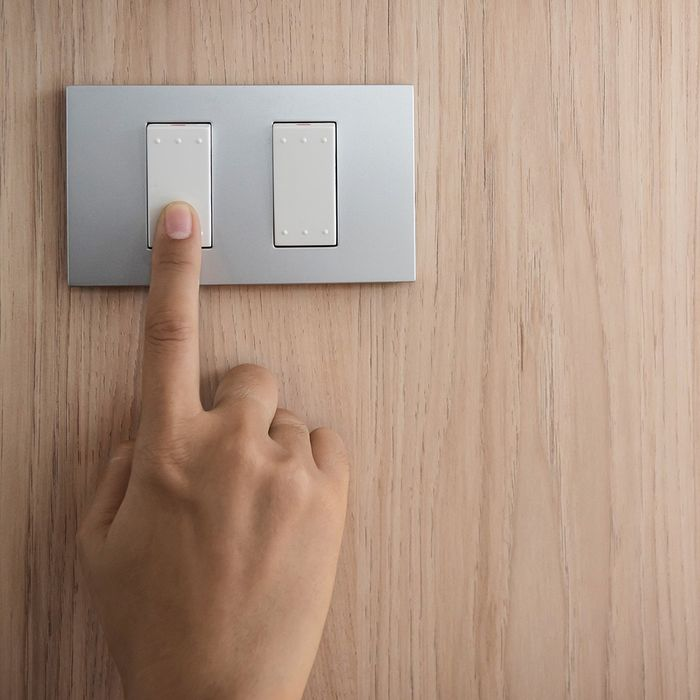 Someone changing their home light switch to save energy.