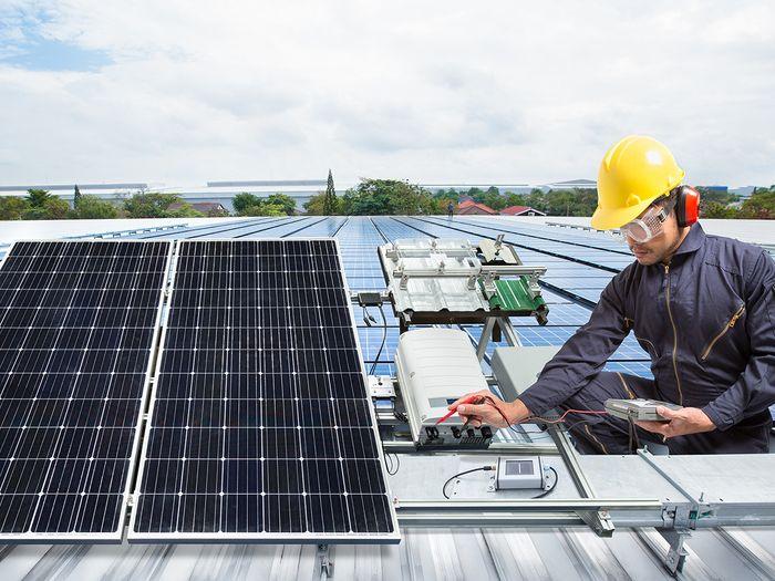 A contractor installs rooftop solar panels.