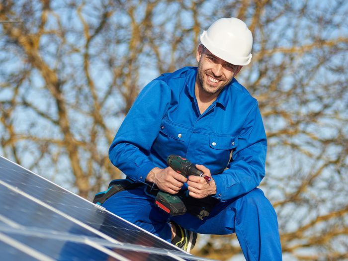 A male solar technician installing rooftop solar panels on a home.