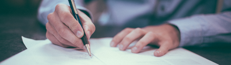 Person signing paperwork with a pen