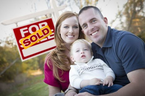 a couple holding their toddler in front of a sold sign