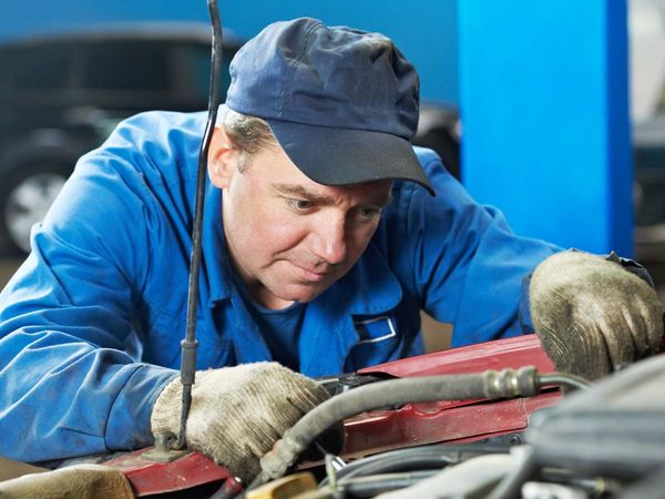 Car technician working underneath the hood of a car.