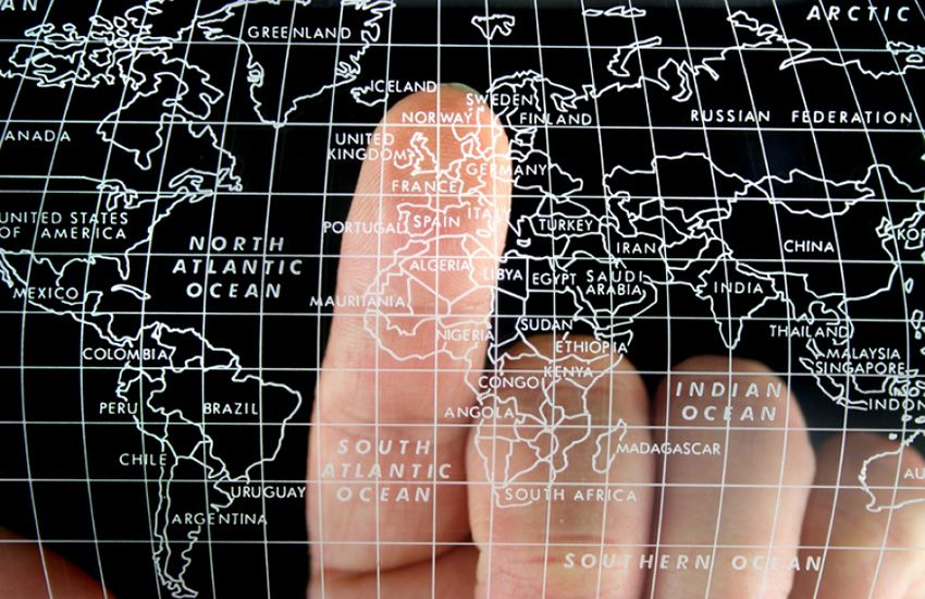 image of a finger pointing on a globe
