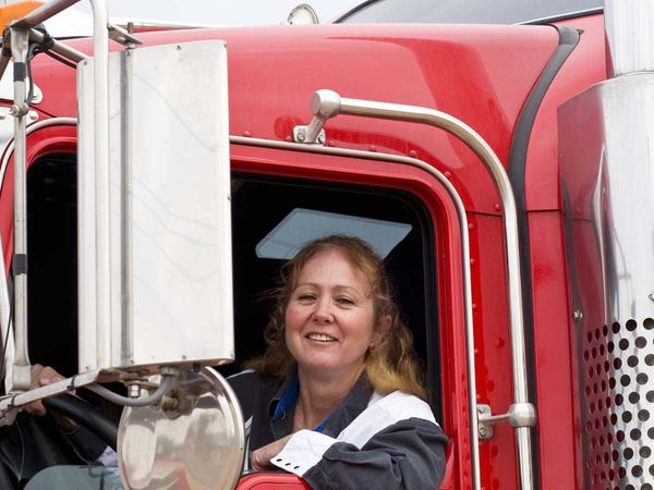 Truck driver leaning out the window of a semi and smiling to the camera.
