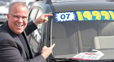 image of a man pointing to a car price tag