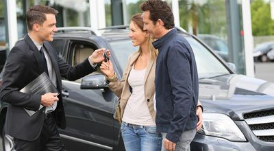 image of a man selling a car to a couple