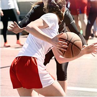 Women playing basketball outside.