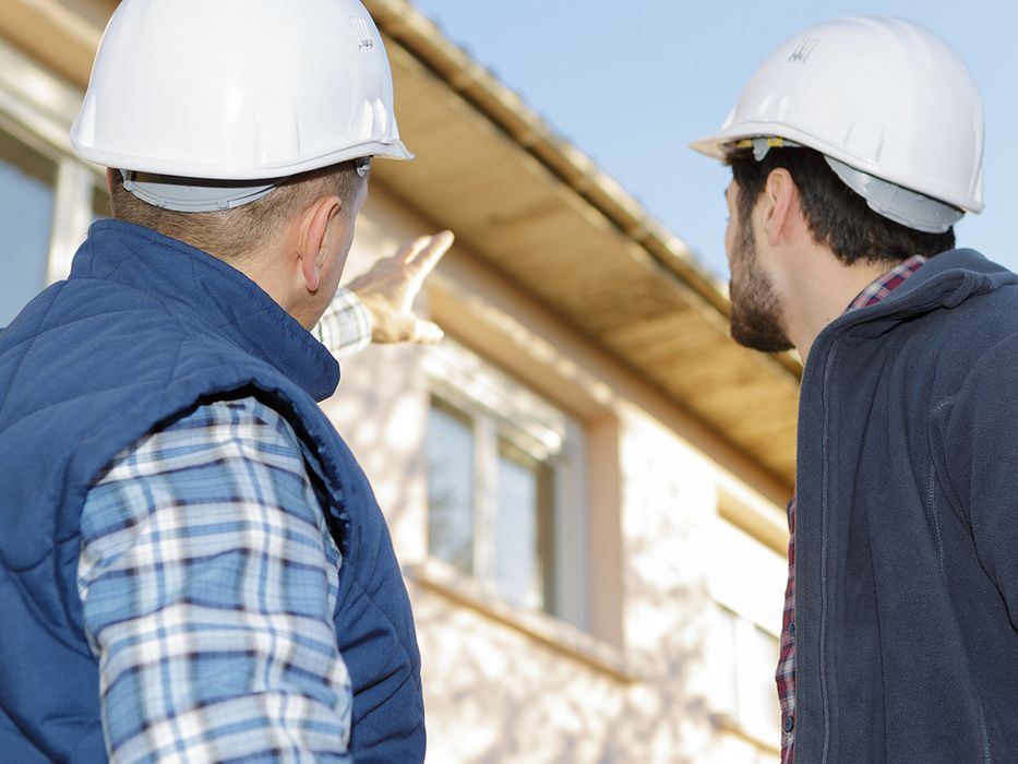 Two men in hard hats pointing to a home.