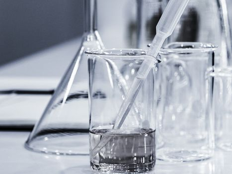 Clear liquid in a glass beaker next to empty beakers