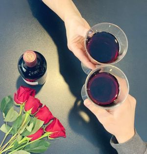 Two hands clink wine glasses together next to long stem red roses.