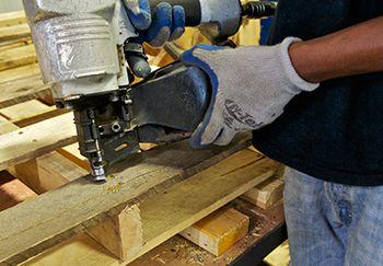 man nailing wood pallet