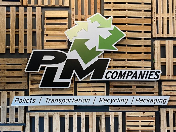 PLM Companies brand logo on a wall of repurposed pallets.