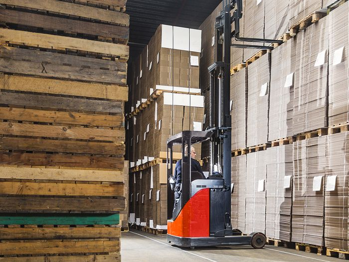 Man operating forklift in warehouse.