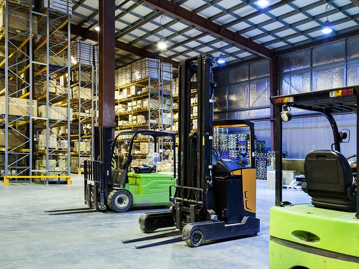 Fleet of forklifts in a warehouse.