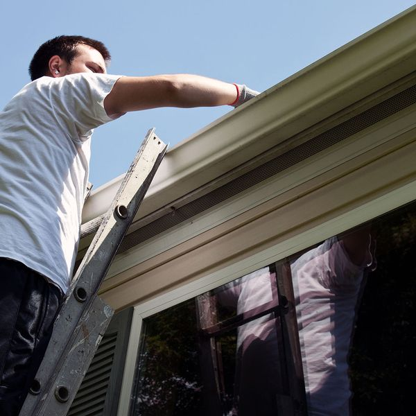 Man clearing a home's gutters on the rooftop