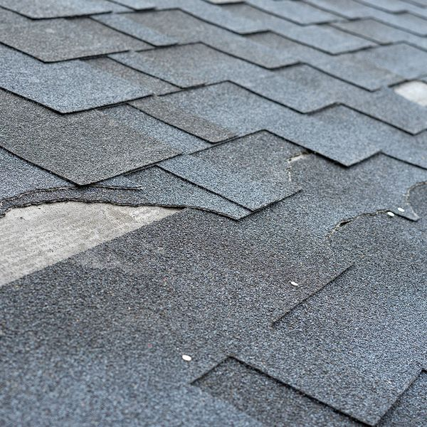 Damaged roof with broken shingles