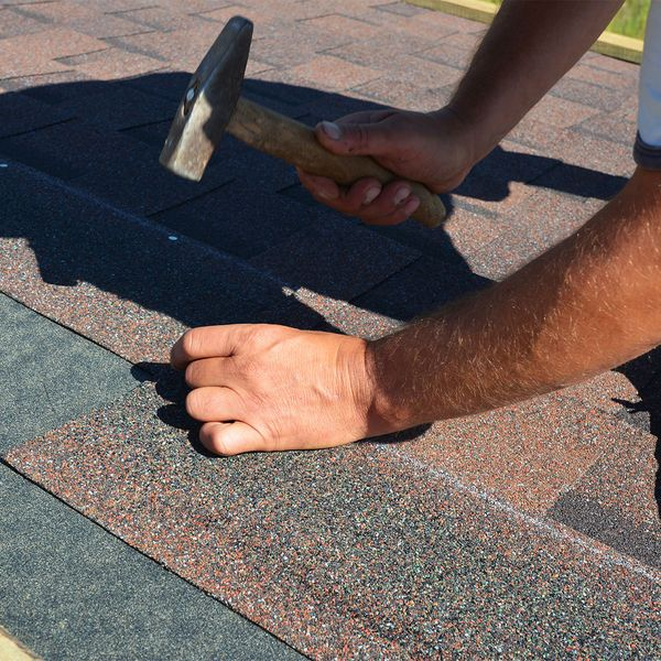 Roofer installing shingles on client roof