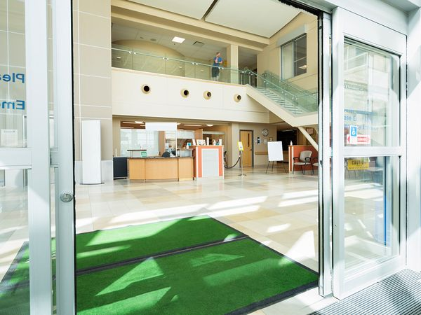 A hospital lobby with clean doormats and floors.