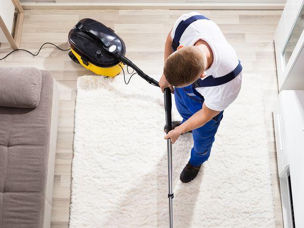 A man cleans his apartment's carpet rug.
