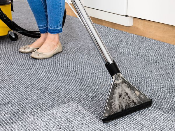 A woman cleans carpeting in an office building.