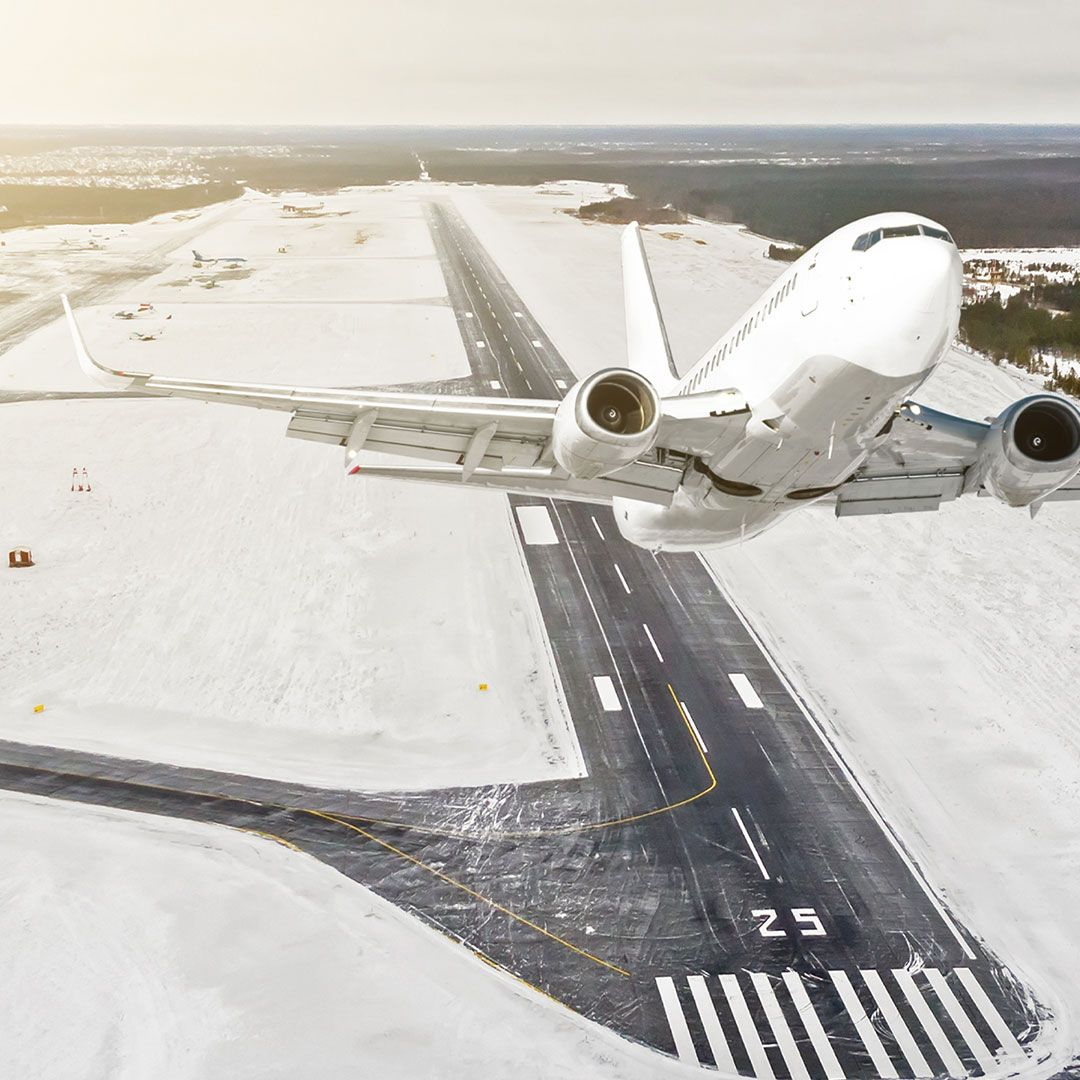 Airplane is climbing flight level high view in the air, against the background of the winter airport of the runway, city, snow, forests, and roads