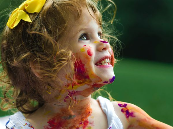A toddler playing with paint.