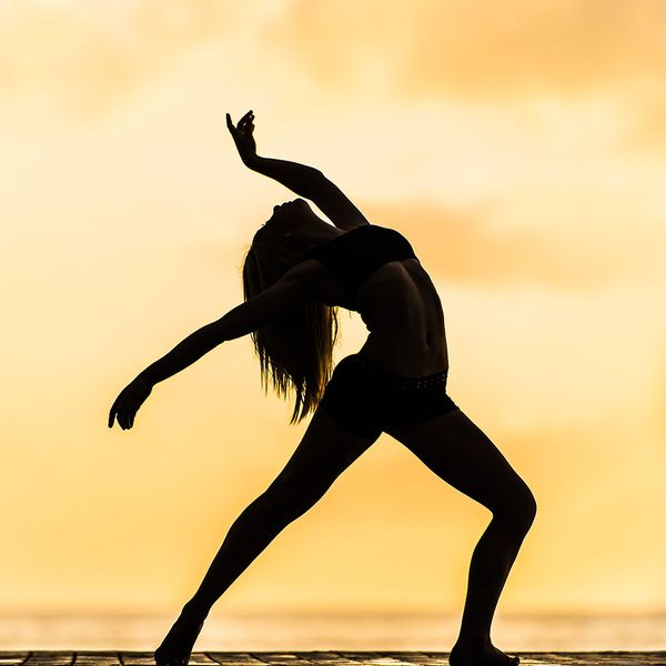 A silhouette of a woman stretching in a yoga pose