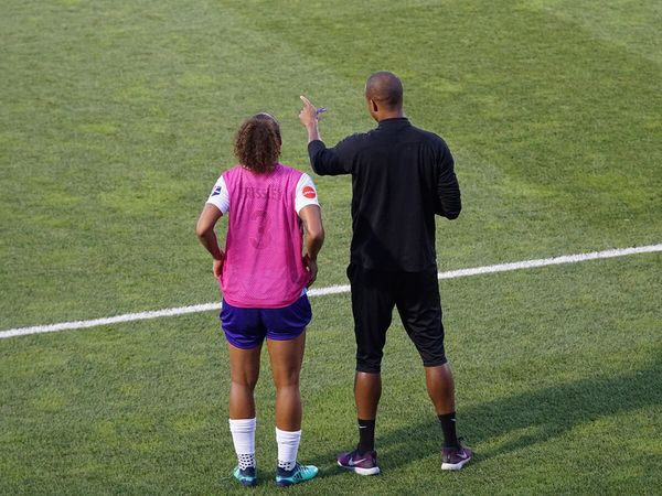 A soccer player discusses strategy with her coach.
