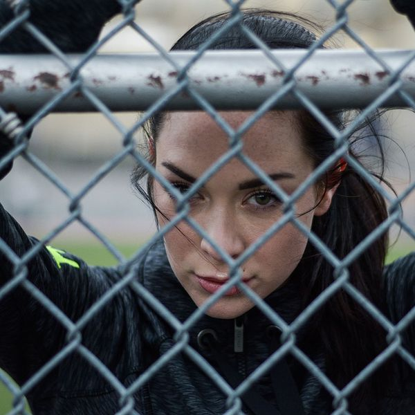 A woman looking through fence